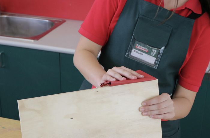 Woman sanding the edge of a sheet of plywood