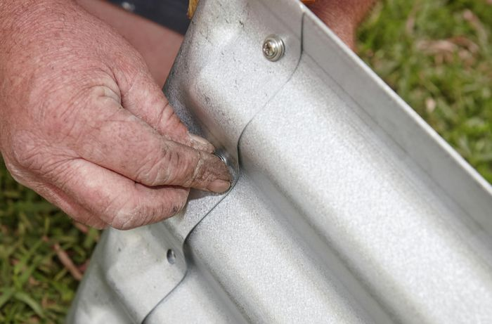 Person screwing corrugated iron garden bed sides together.