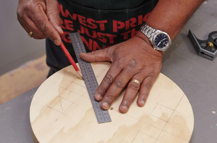 Positions for stool seat legs being marked with a ruler and pencil