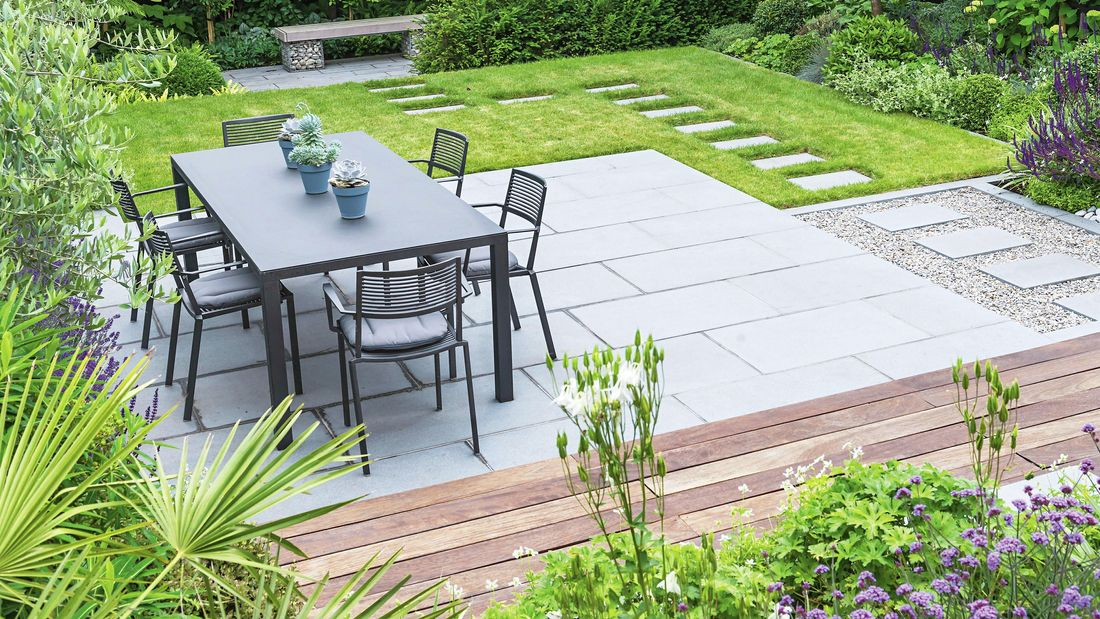 A completed outdoor dining area, complete with paved area, stepping stones and wooden benches