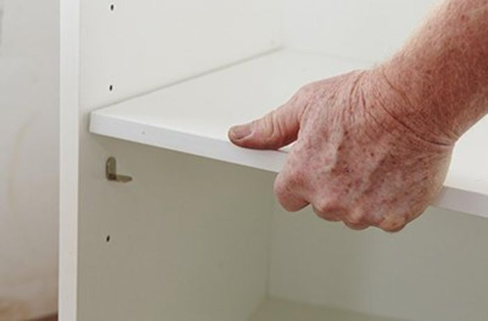 A shelf being laid in a cabinet