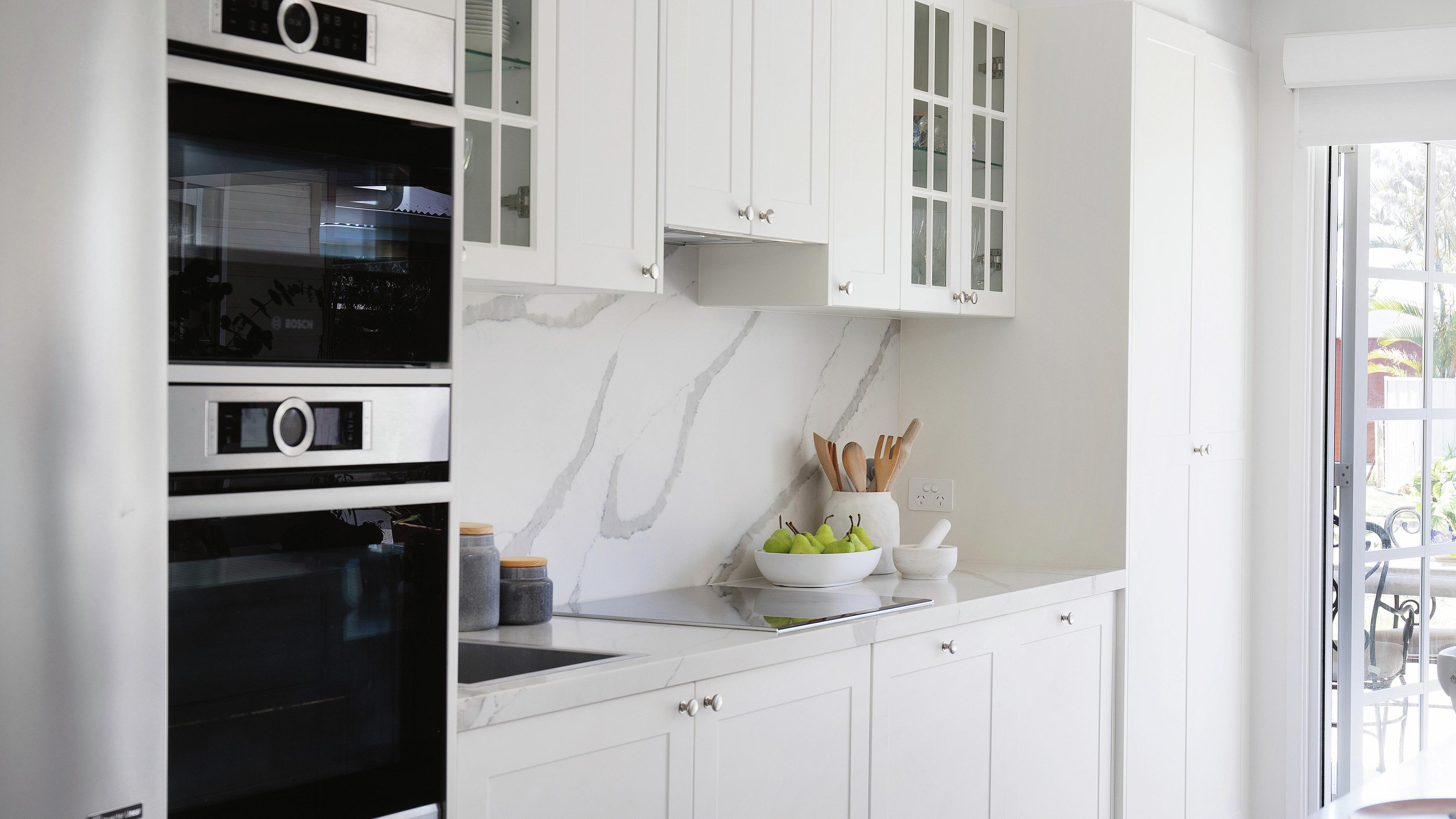 Shaker-style cabinets in a modern white kitchen.