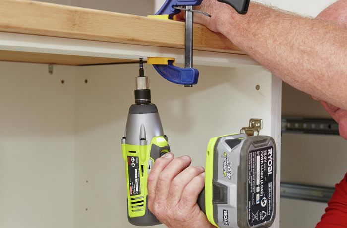 Person drilling benchtop onto cabinet