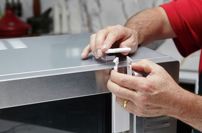 A person attaching a childproof lock to a microwave oven