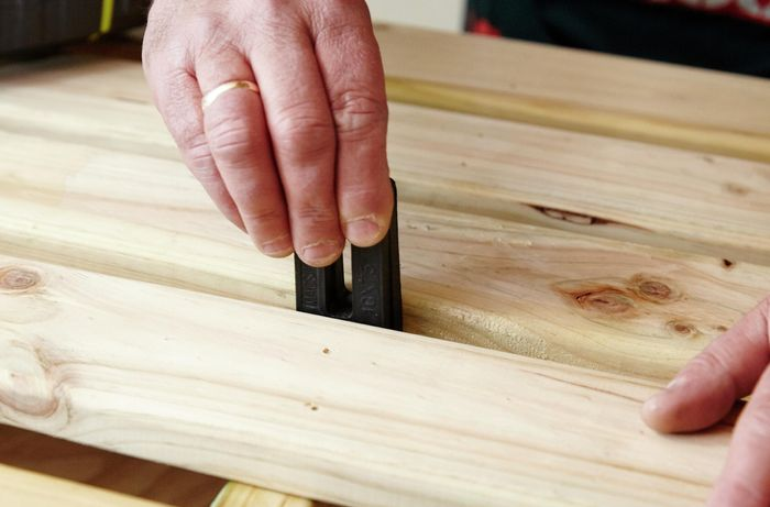 A person using a spacer to position decking boards