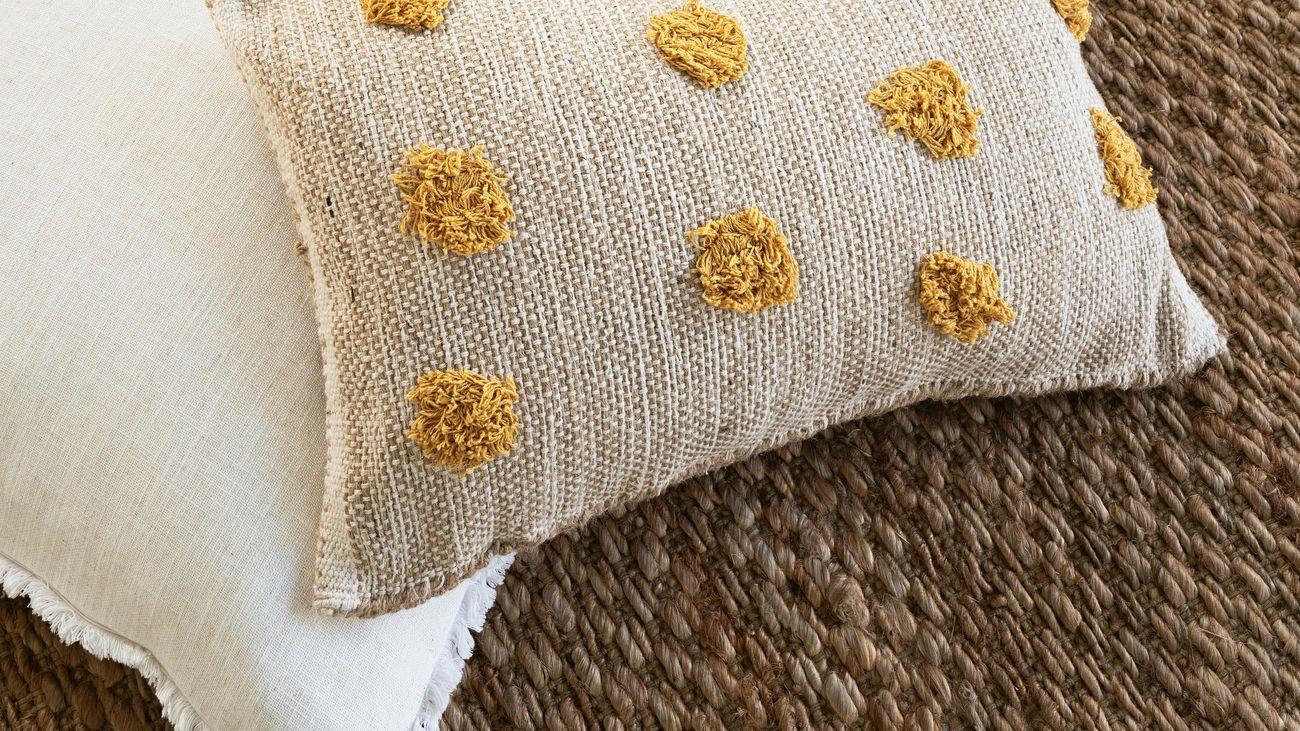 White and jute pompom cushions on a jute rug
