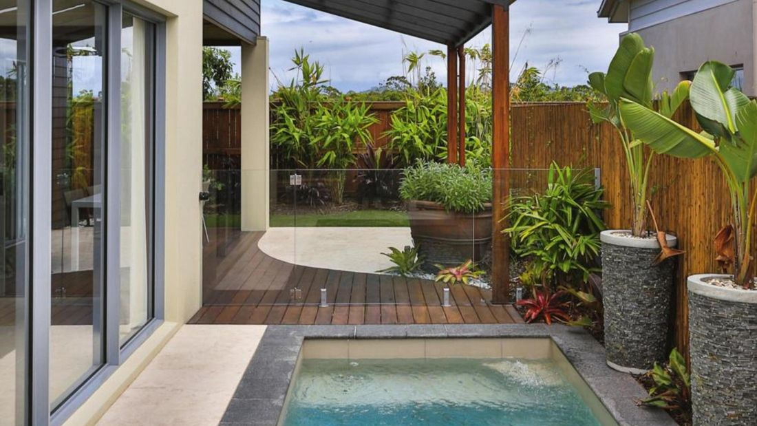 Outdoor lap pool surrounded by lush plants.
