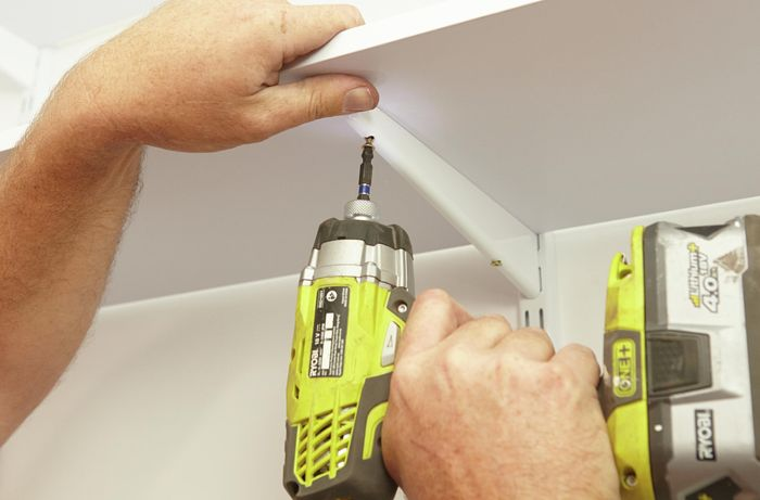 Connecting the shelf brackets to the upright wall bracket with a Ryobi drill