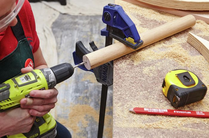 A person drilling a hole in a piece of dowel using a cordless drill