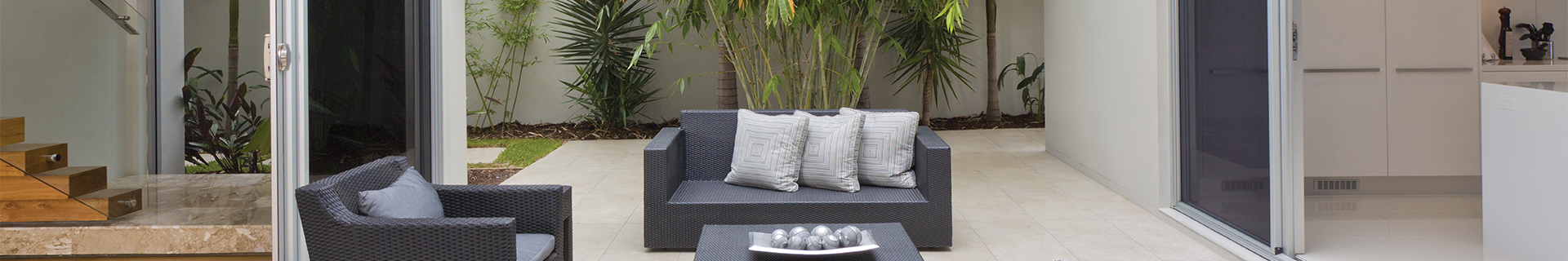 Outdoor area with couch, table and plants.