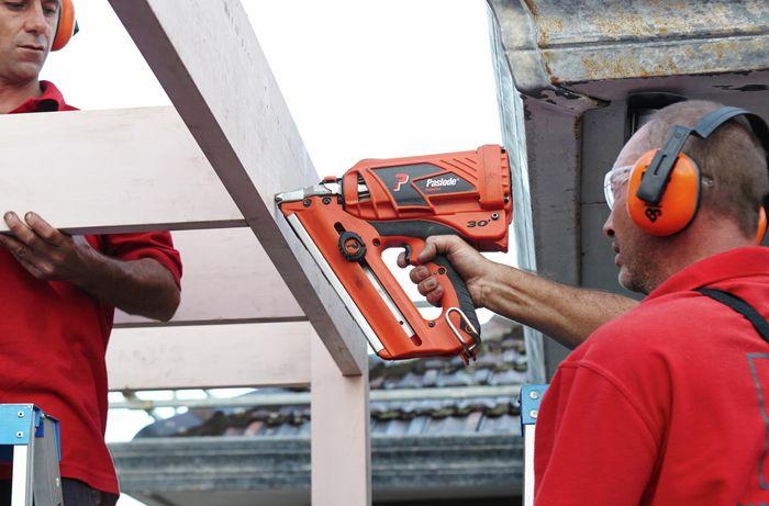 Person drilling into carport frame.