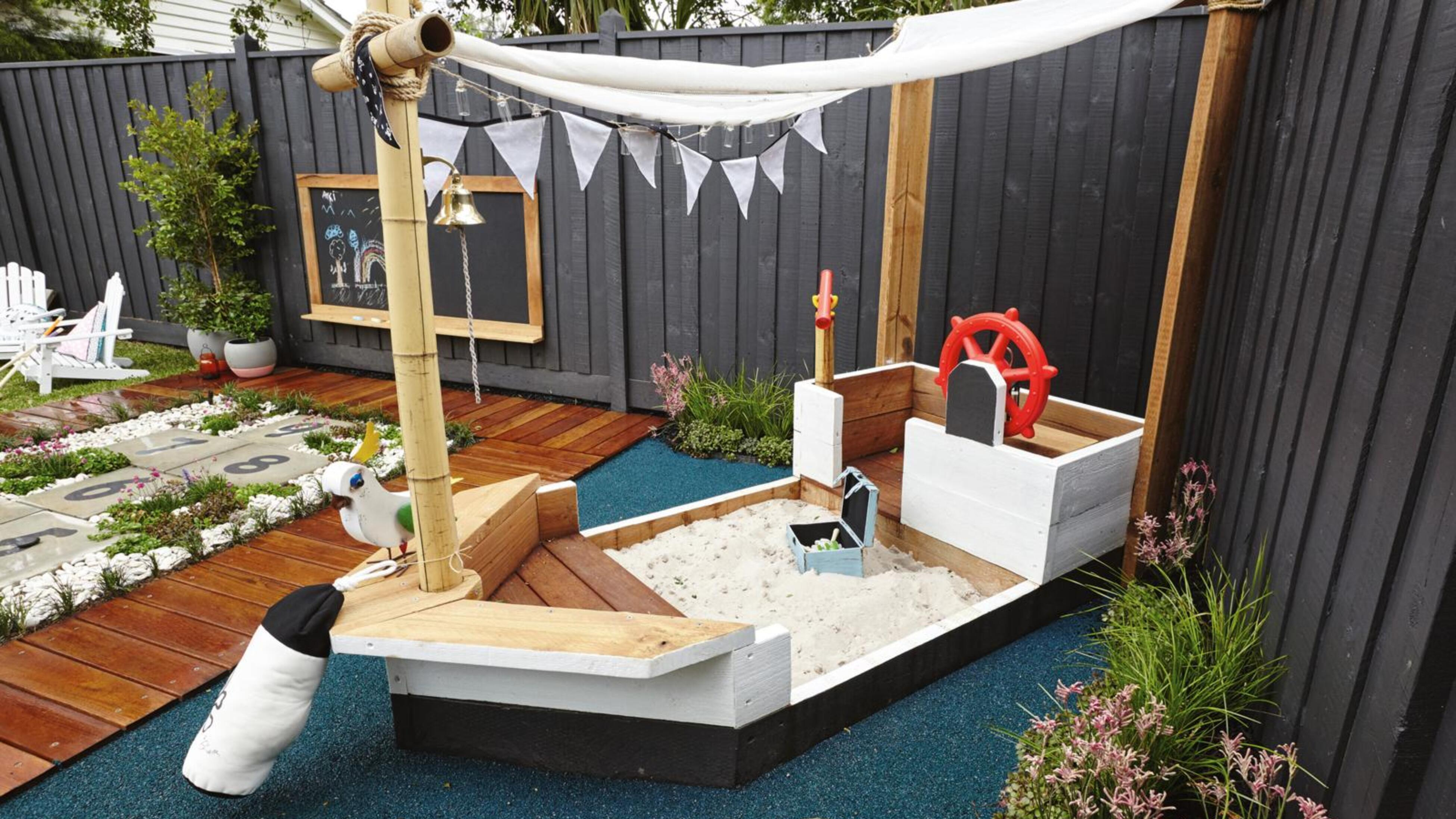 Backyard area with pirate ship play area, hopscotch and chalkboard on fence.