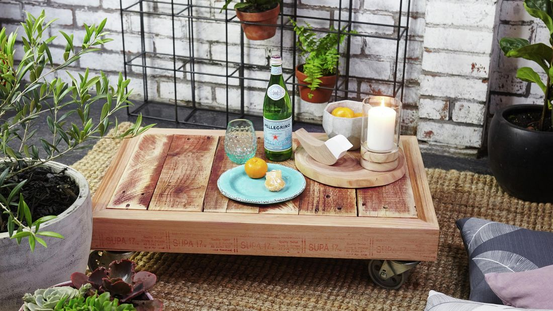A completed outdoor pallet coffee table, complete with glassware, plate, oranges and a bottle of Pellegrino