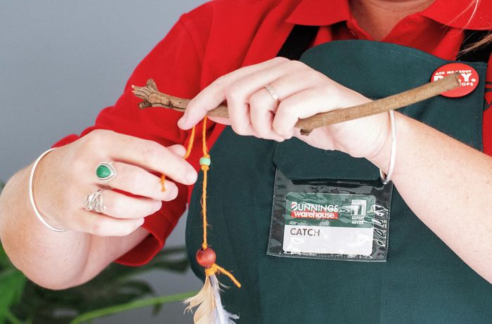 Tying the decorated piece of string to the stick.