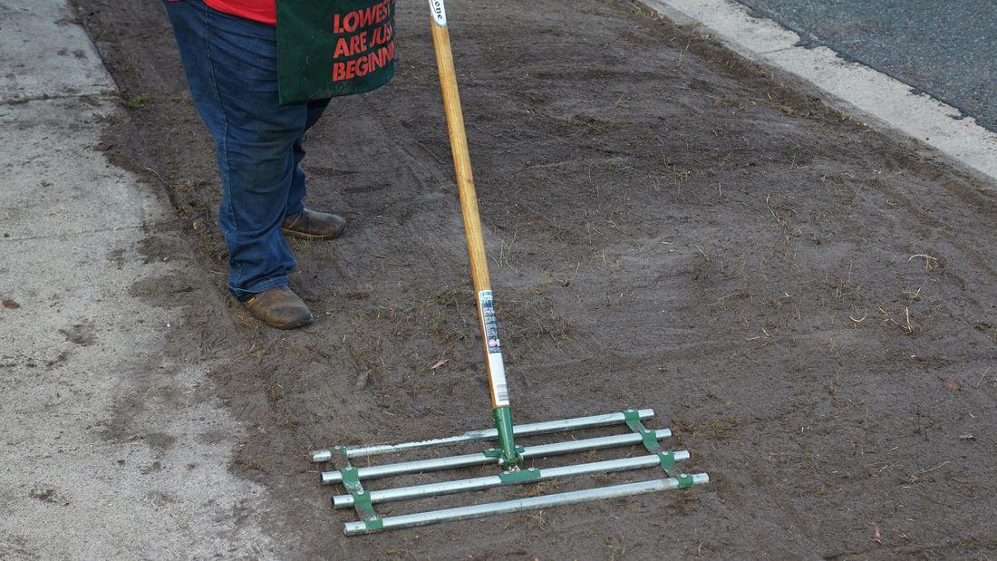 A person raking soil