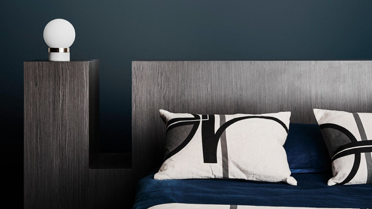 Bedroom with dark blue walls and a timber bedhead.