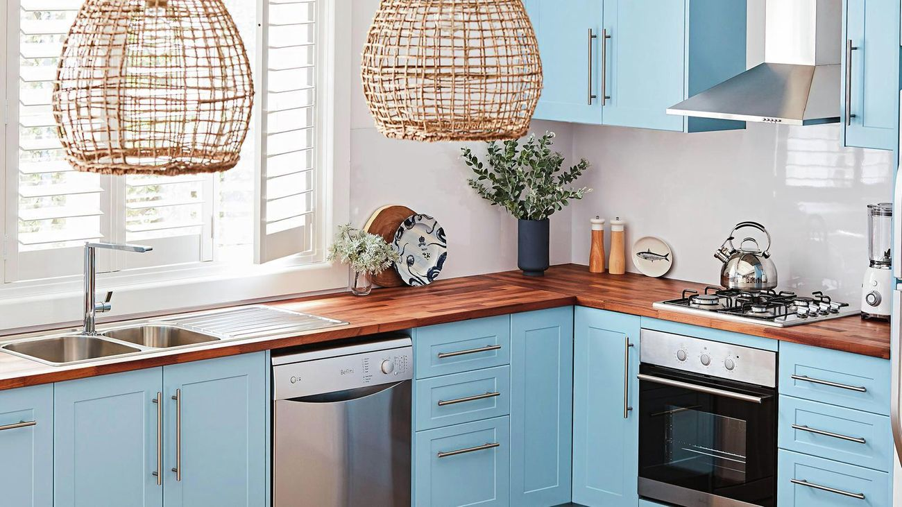blue kitchen cabinetry, timber benchtop and rattan pendant lights