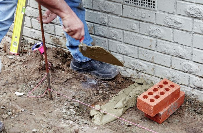 A person laying a line of mortar on the ground at right angles to a house wall