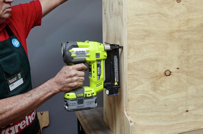 Person using nail gun to nail piece of timber together