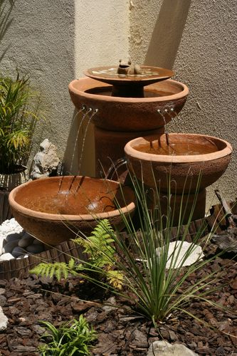 Descending diagonal pots on a wall with water trickling from one to another