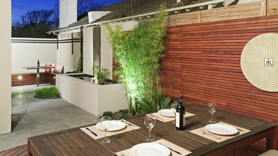 Outdoor dining area with timber screening, water feature and timber dining furniture