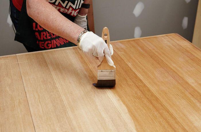 Bunnings Team Member applying varnish to the table
