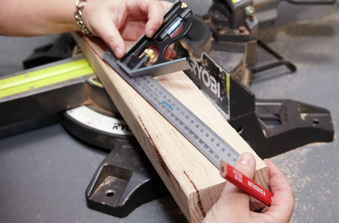Person using ruler to measure a cut to be made on piece of timber