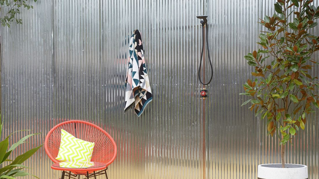Outdoor shower area with orange wire chair and towel hanging off hook.