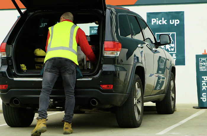 Bunnings TM loading items into a car out the front of a Bunnings store