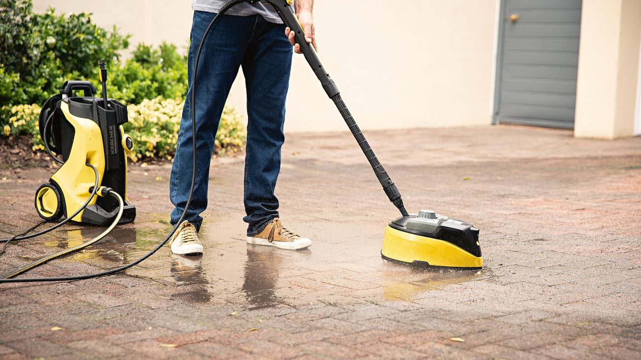 A person cleans outdoor pavers with a Kärcher water blaster
