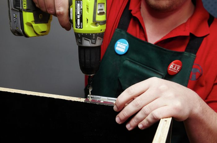 A person attaching a hinge to a plywood box using a cordless drill