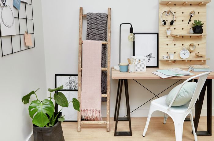 Home office with desk, chair, plant, timber ladder, and pegboard shelf.