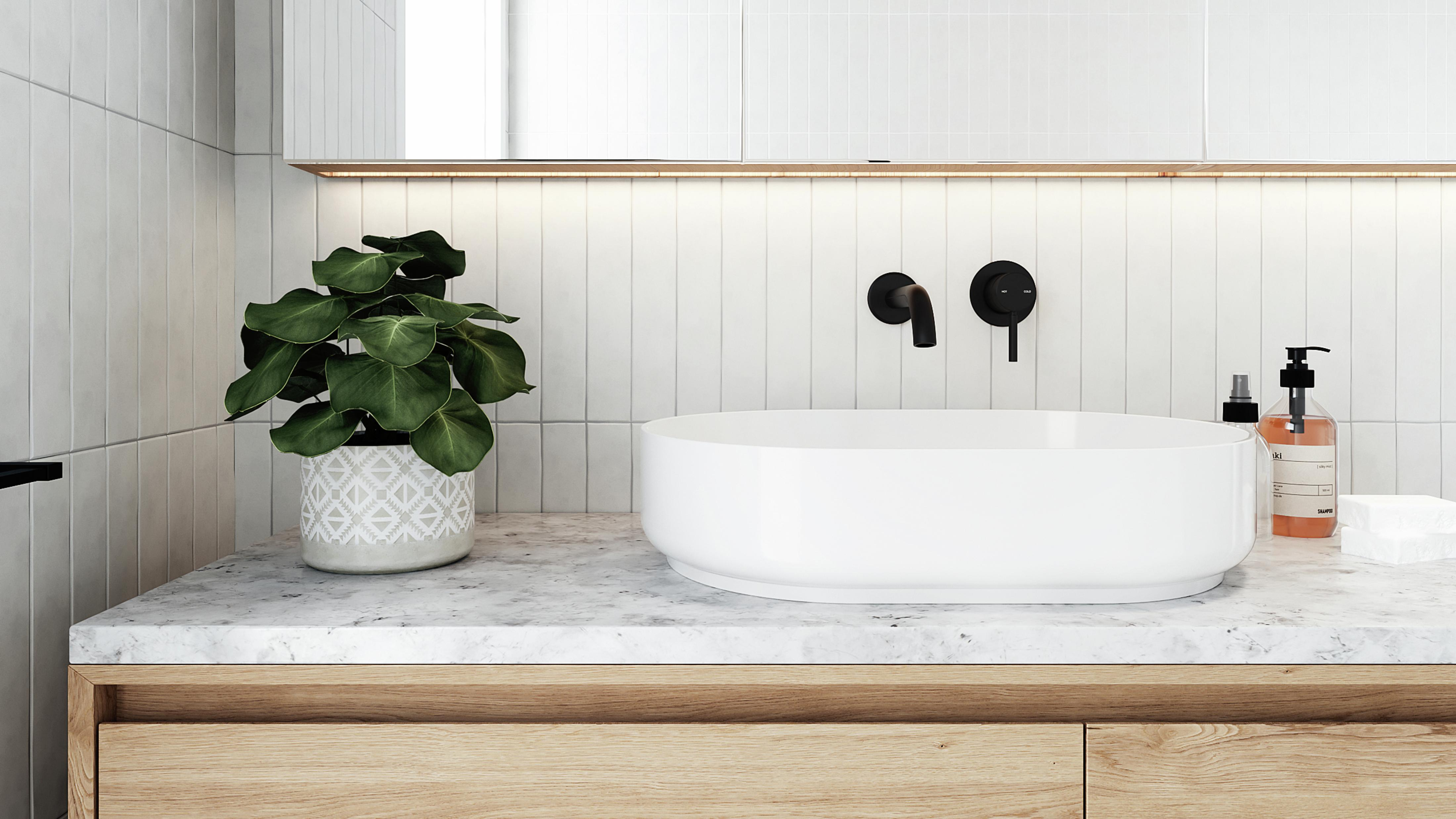 Bathroom featuring countertop basin, black tapware, plant and timber cabinetry.