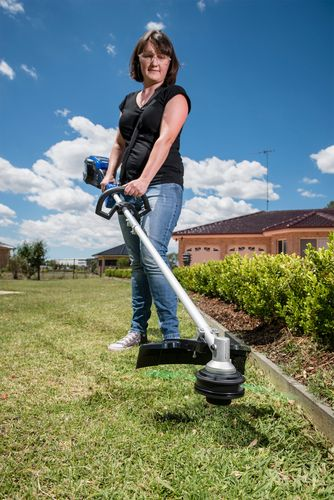 A woman using a Victa line trimmer to cut grass near a wooden garden bed border