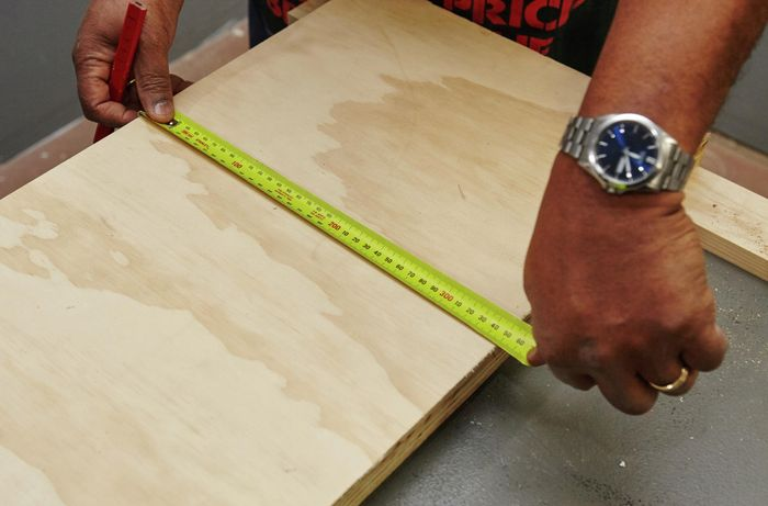 A panel of wood being measured for a bar stool seat to be cut from it