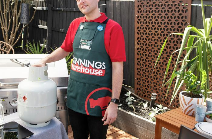 A person standing beside a gas bottle next to a BBQ