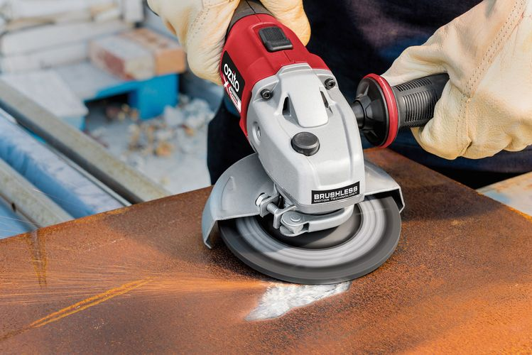 Person using cordless angle grinder to cut metal