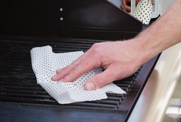 Person cleaning barbecue with wipe