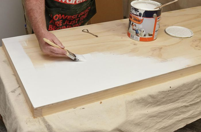 A person painting a plywood panel white