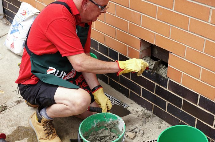 Spreading a reasonably thick layer of mortar for the vent to rest on