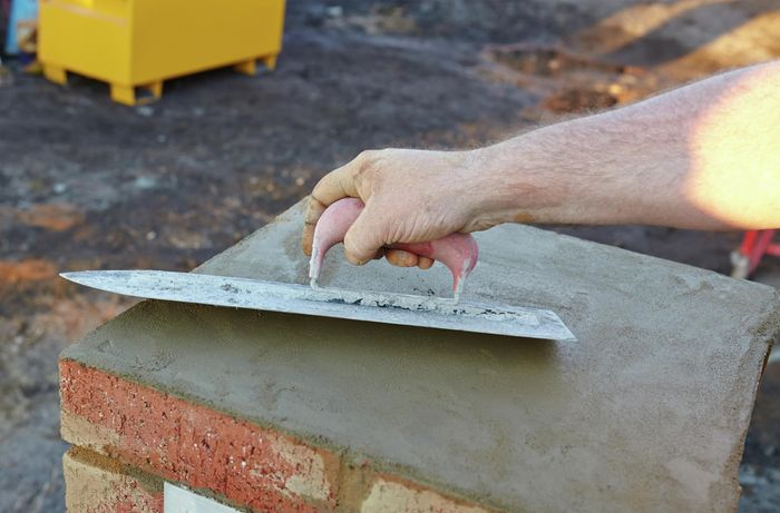 Cement on top of a brick mailbox being smoothed out with a trowel