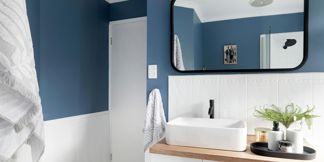 Bathroom with white tiles, blue wall, timber-top vanity and black tap.