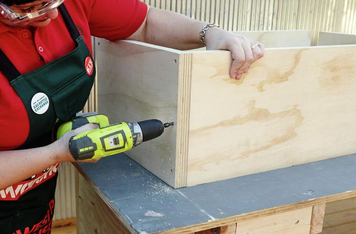 A person attaching plywood panels using screws and a cordless driver