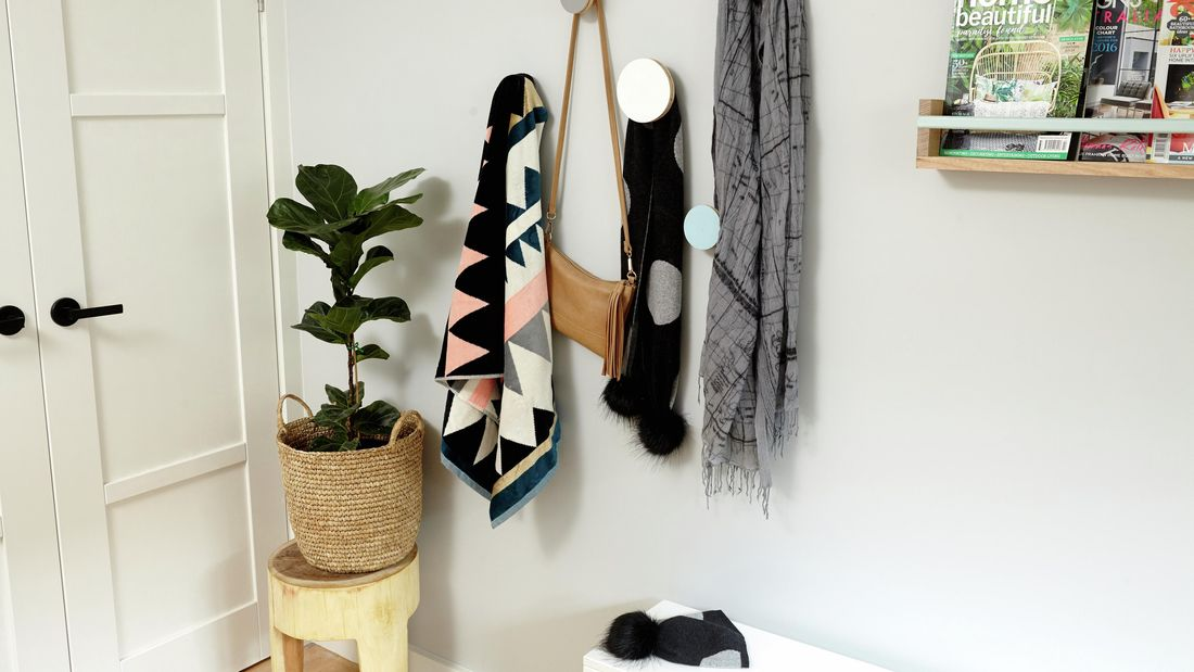 Clothing and bags hanging on round hooks on a bedroom wall