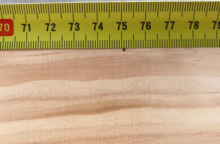 Close-up of a measuring tape and pine timber with a mark at 751 millimetres