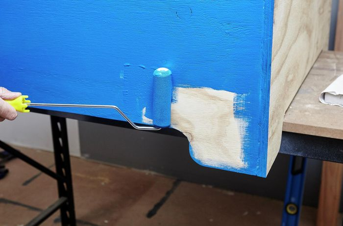 Person painting timber blue using roller brush