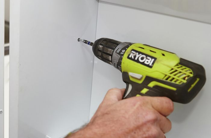 Securing the side panels with a Ryobi drill.