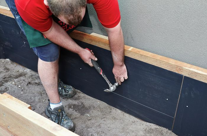 Person securing black plastic lining to sides of DIY raised garden bed.