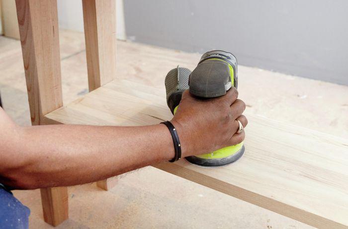 Person sanding table using sander