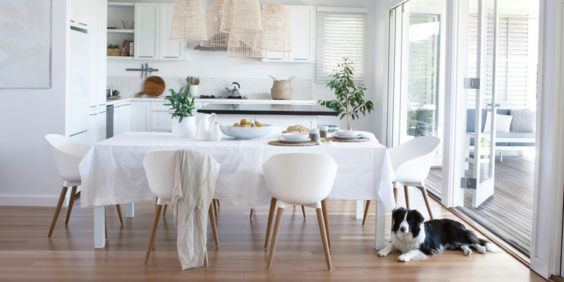 Dining room with hardwood floors, dining table and white chairs.